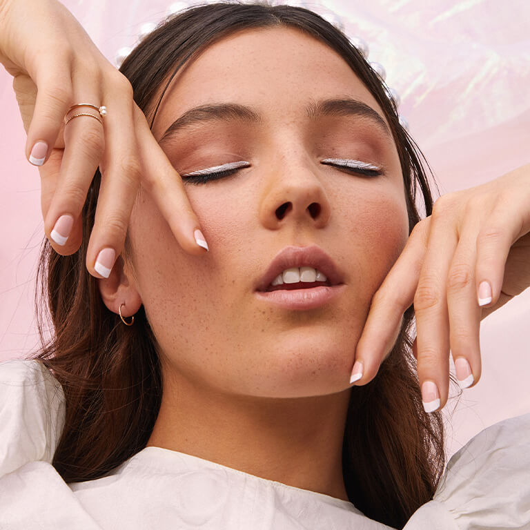 A closeup image of a model with a white eyeliner look and French tip mani posing with her two hands