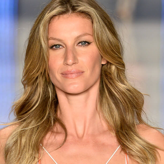Close-up image of Gisele Bündchen rocking blonde, wavy hairstyle on the runway
