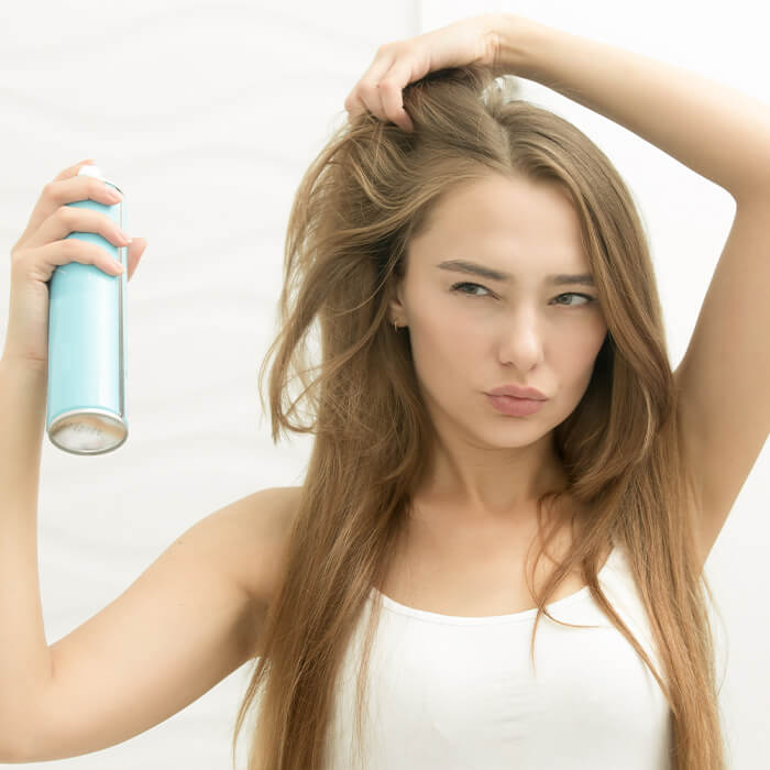 Young woman applying hairspray on her hair