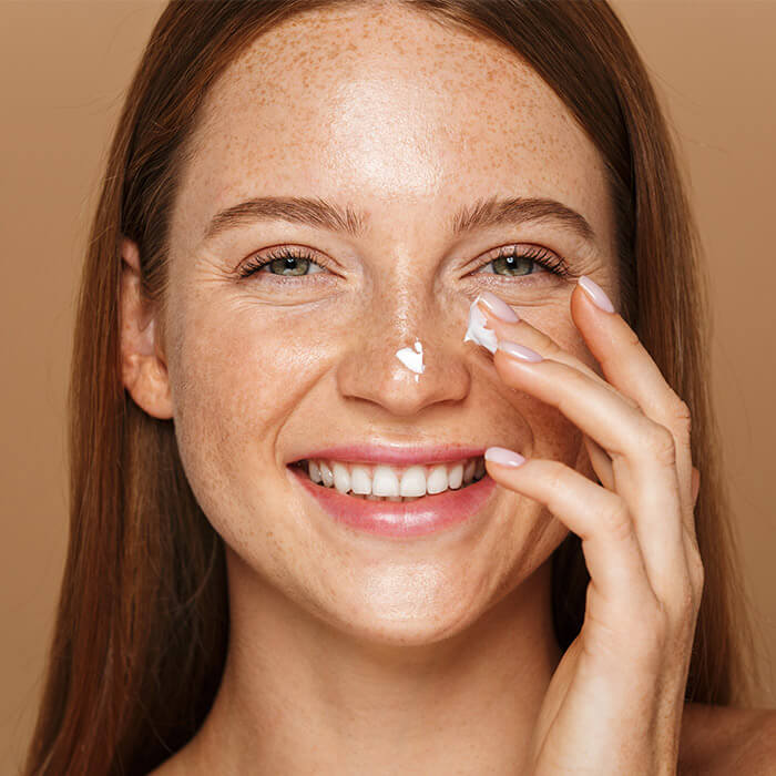 Close-up of a smiling woman applying face cream against brown background