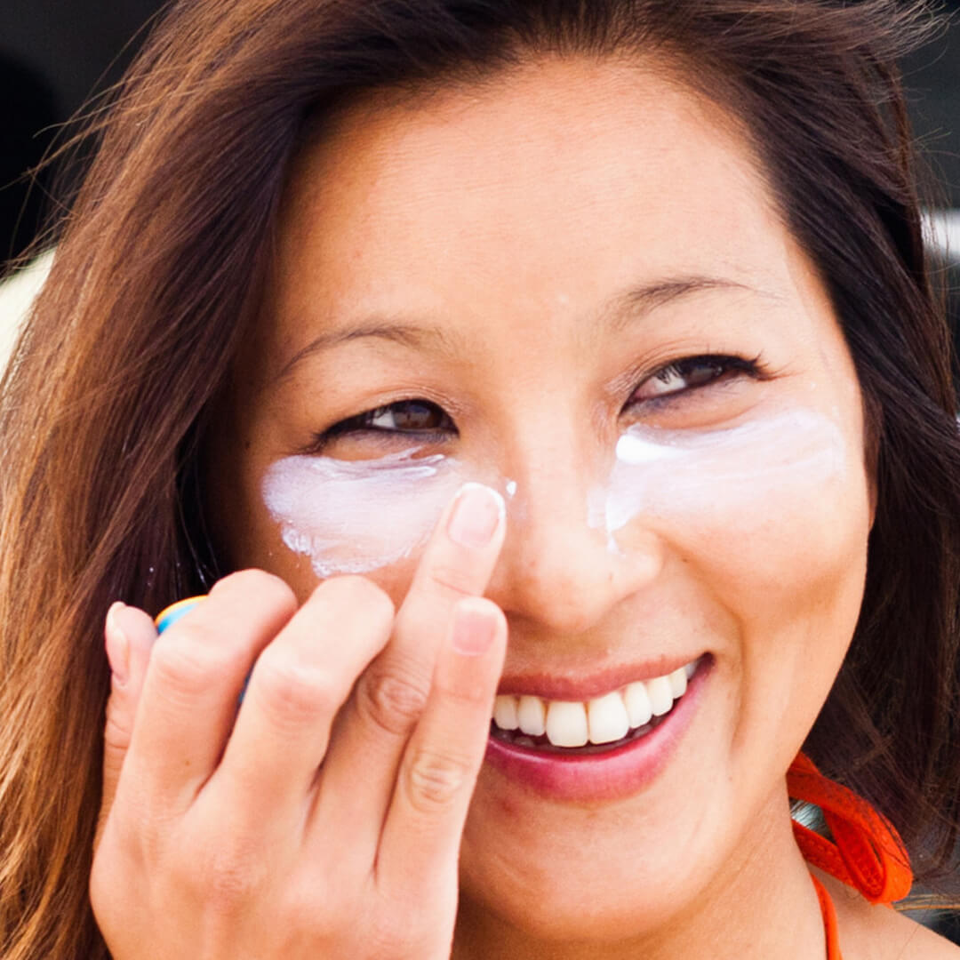 Image of a woman putting white cream under her eyes