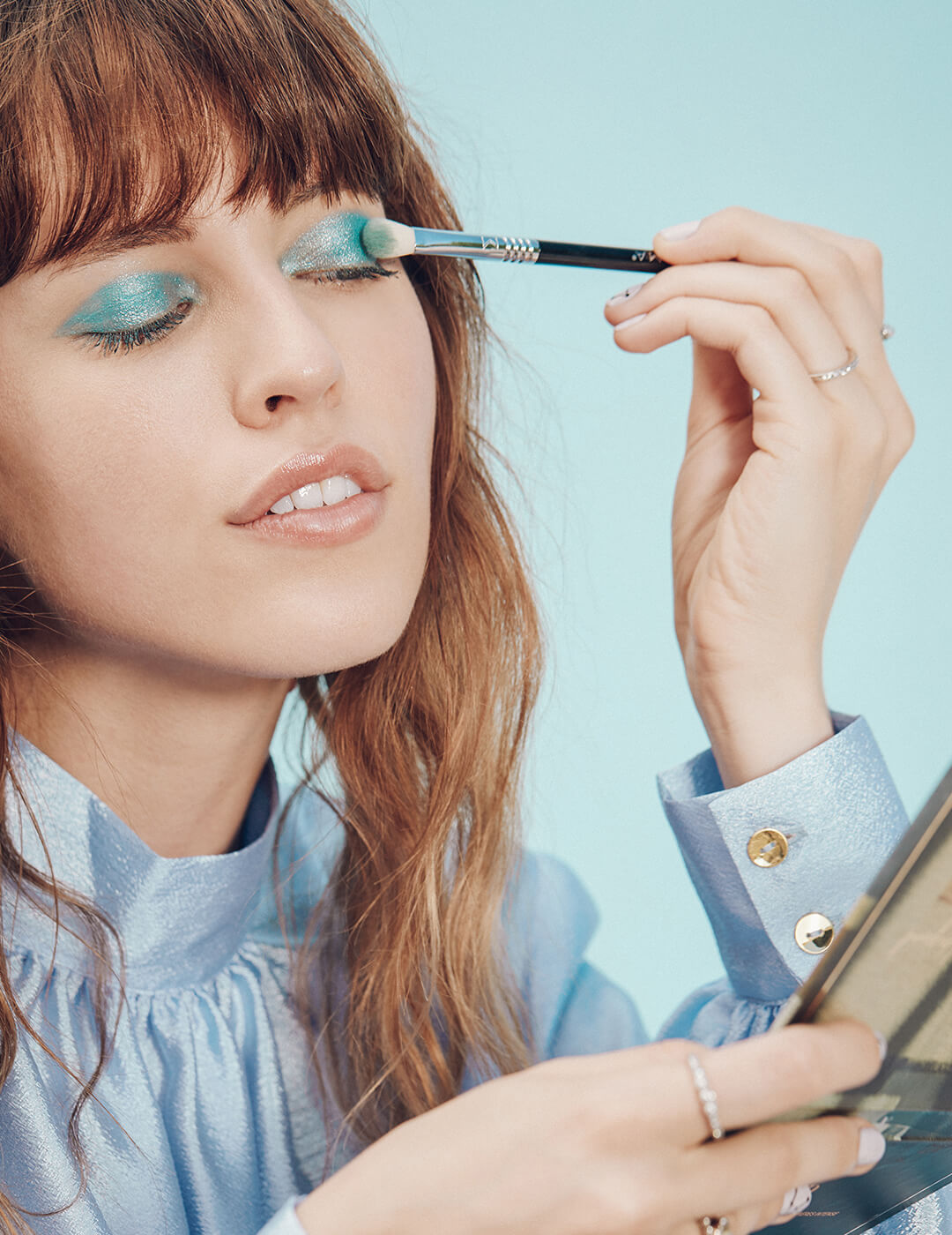 An image of a model putting shimmery blue eyeshadow with a makeup brush