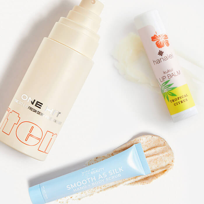 Image of ITEM BEAUTY One Hit Triple Action Setting Mist, HANALEI COMPANY Kukui Lip Balm in Tropical Citrus, and GLOW ON 5TH Smooth As Silk Hand + Body Scrub swatched on white background