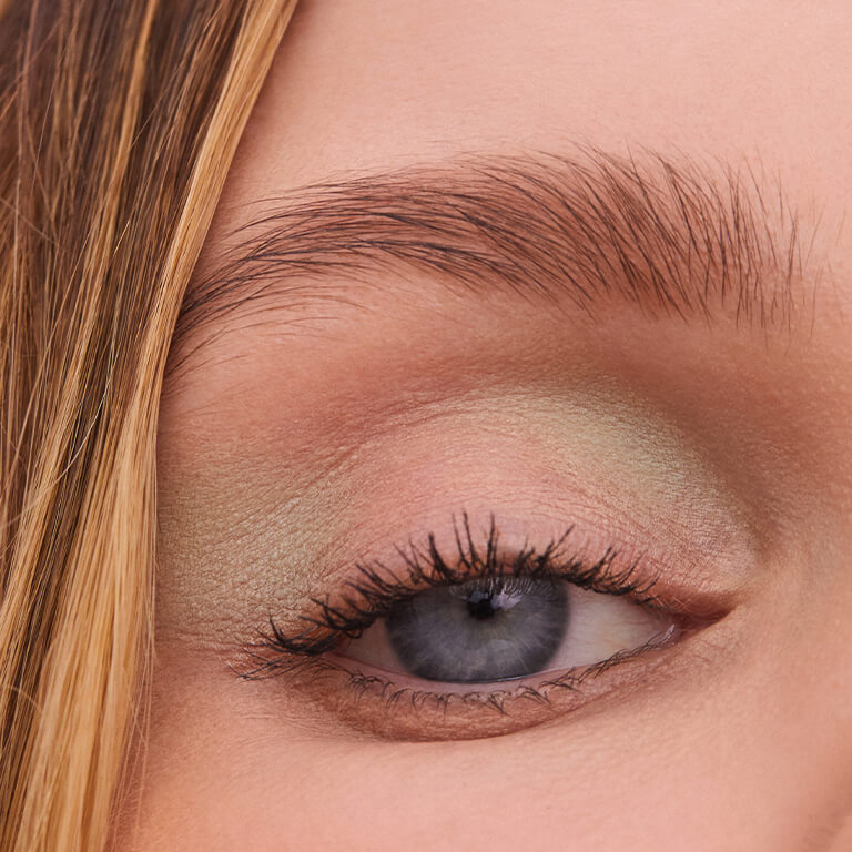 A closeup image of a model's eyebrows and mint green eyeshadow look
