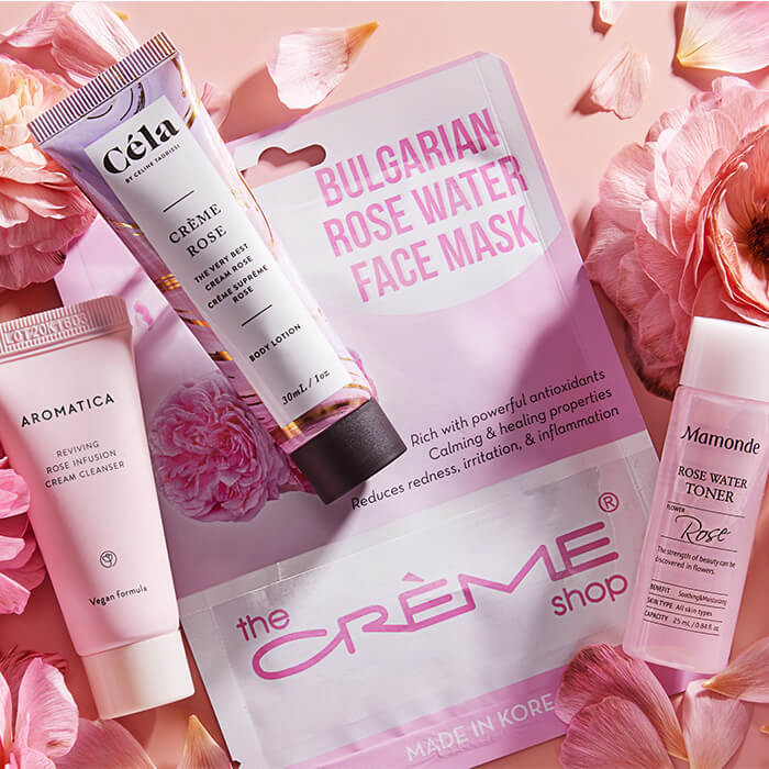 Image of THE CRÈME SHOP Bulgarian Rose Water Face Mask, AROMATICA Reviving Rose Infusion Cream Cleanser, CÉLA Crème Rose, MAMONDE Rose Water Toner, and rose flowers and petals on pink background