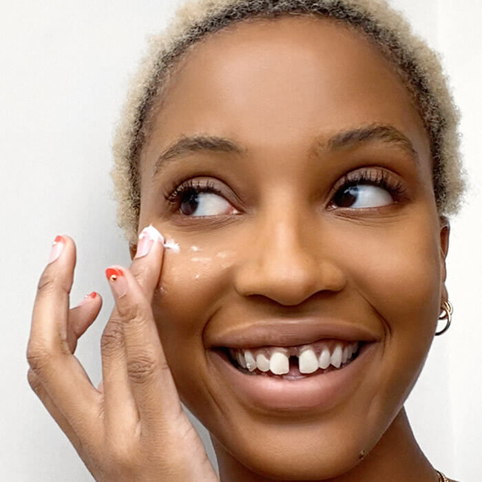 An image of a woman putting on cream under her eye