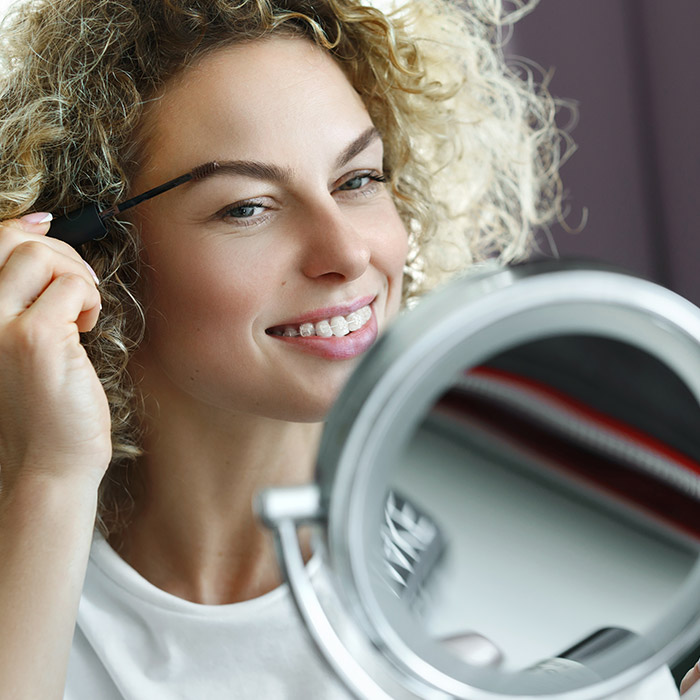 A photo of a woman using an eyebrow tinting brush
