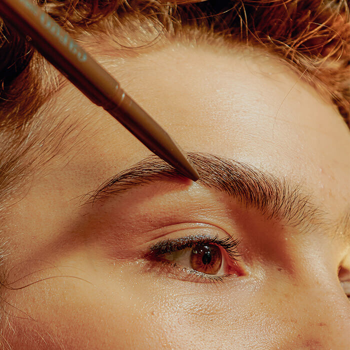 Close-up of a woman filling in her eyebrow with a eyebrow pencil