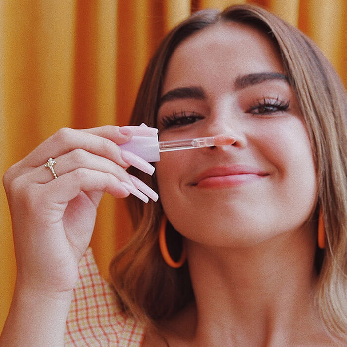 Image of Addison Rae smelling the ITEM BEAUTY Lip Quip in Come Thru