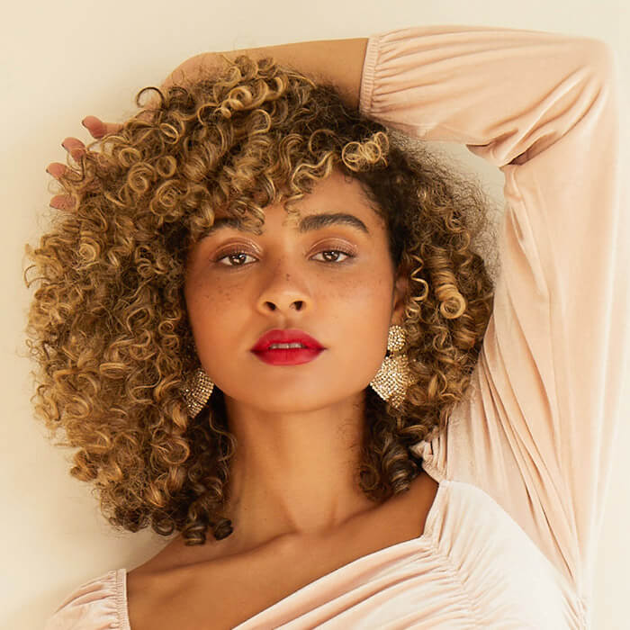 Image of a model with curly hair posing against cream background