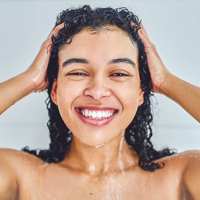 Close-up image of a smiling woman with curly hair taking a shower in her bathroom