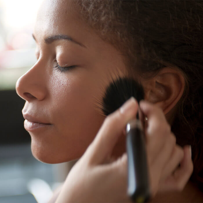 Woman of color being applied foundation on with makeup brush