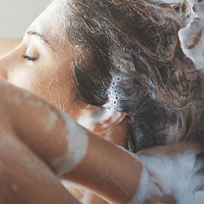 Close-up image of a model lathering shampoo on her hair