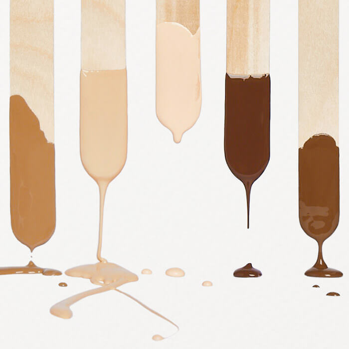 Five popsicle sticks dripping with different shades of liquid foundation