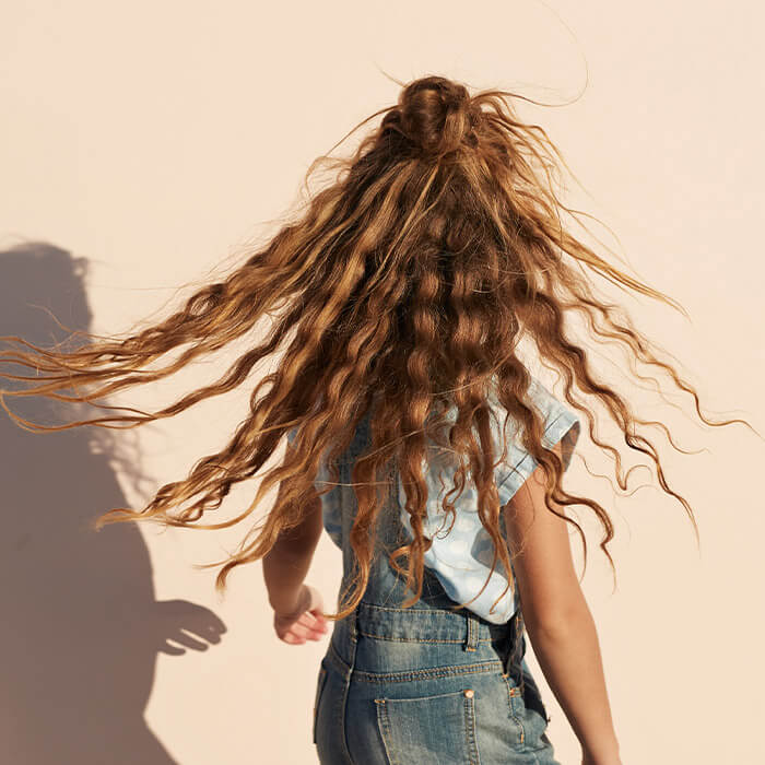 Image of a girl in a denim jumper and light blue shirt with her wavy hair in the air