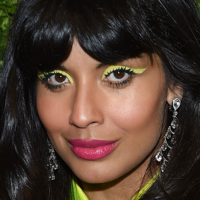 Close-up of Jameela Jamil rocking a slime green eyeliner and bright pink lips makeup look
