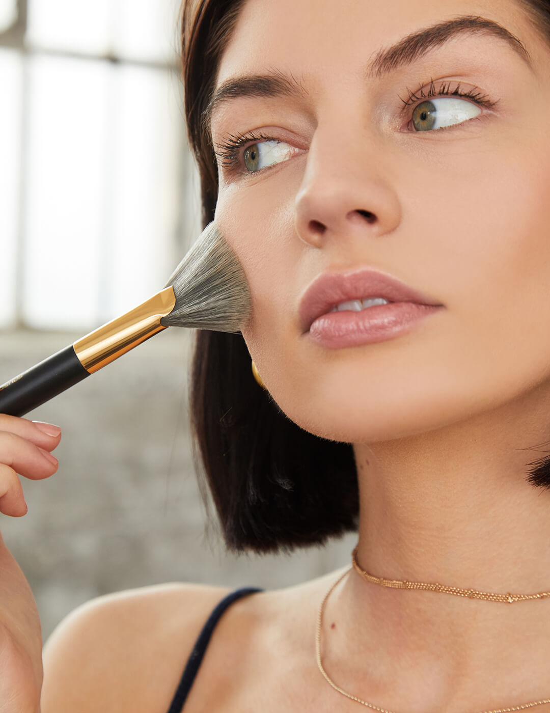 An image of a model touching her cheek with a makeup brush