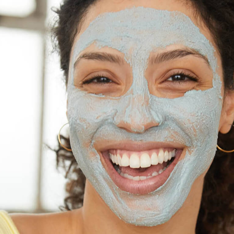 An image of a model with mud mask on her face smiling big