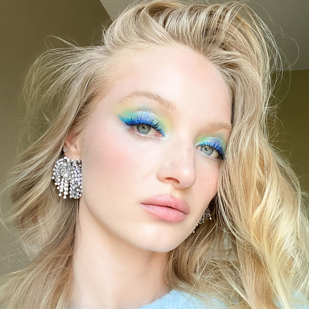 Close-up image of model Ash Walker wearing gem stone studded earrings and bright colorful eye makeup