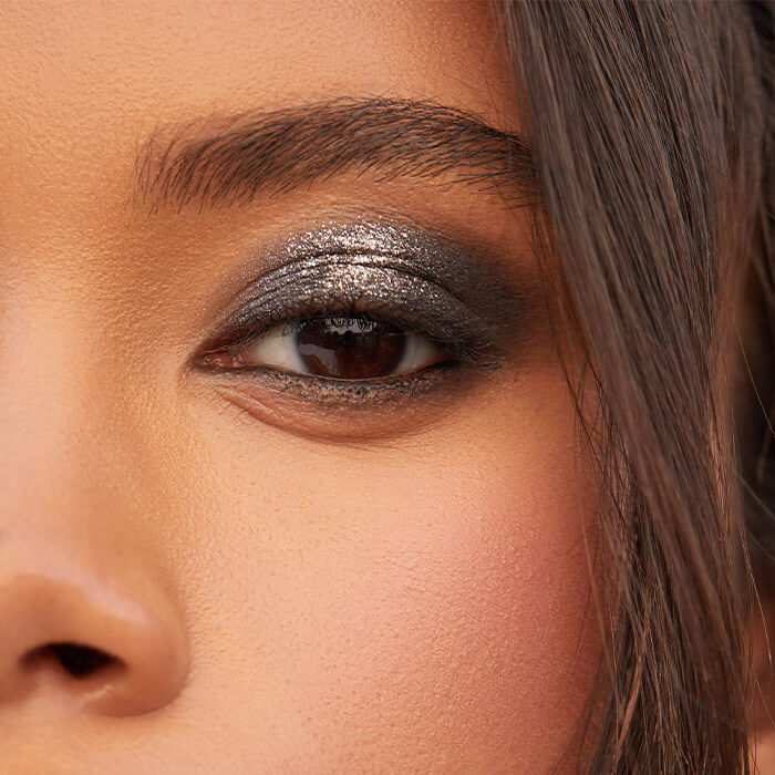 Close-up image of a model's shimmery, smoky eye makeup look