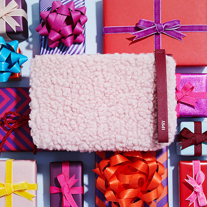 Image of December 2020 IPSY Glam Bag on top of colorful gift boxes of different shapes and sizes