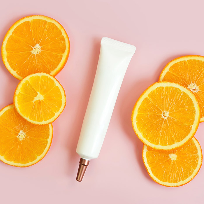 A photo of a serum with orange slices on a pink background