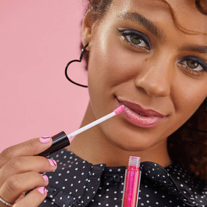 Close-up image of a model wearing a polka-dotted outfit holding a lip gloss