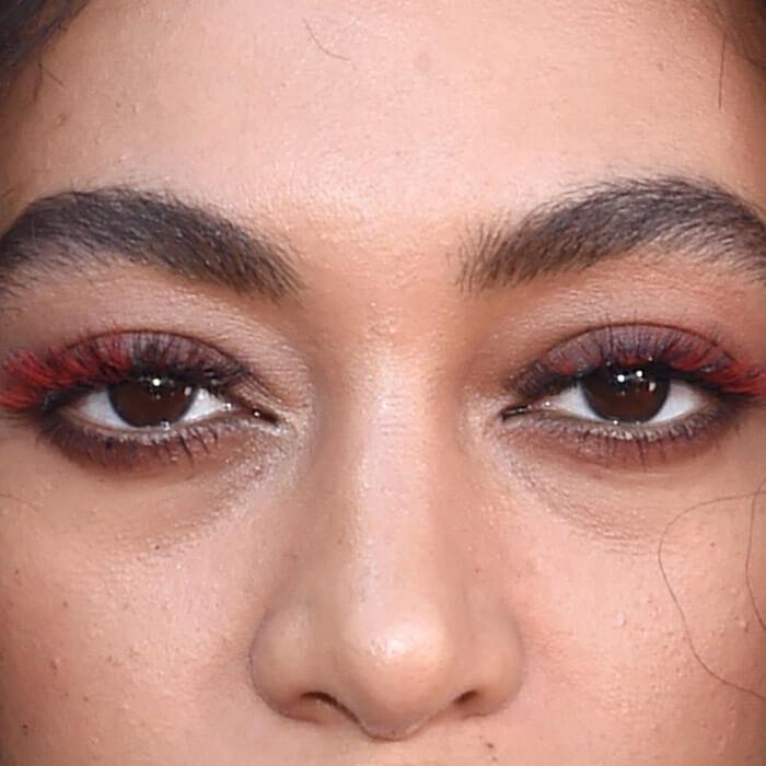 A closeup of a model wearing red mascara