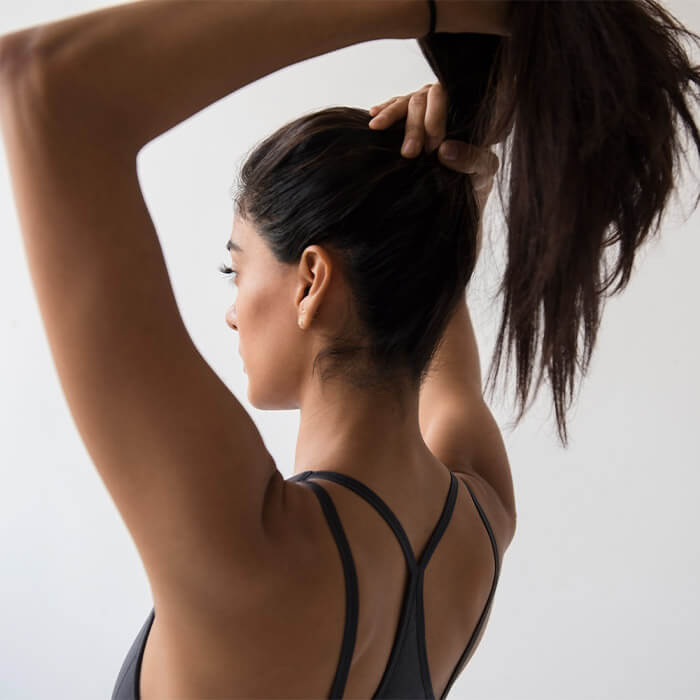 Image of a woman in athletic wear tying her dark hair in a ponytail