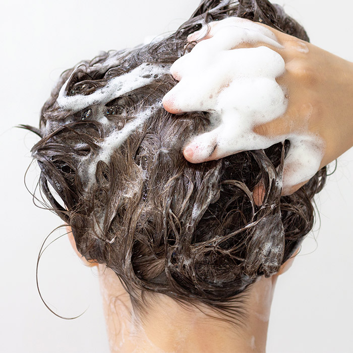 Close-up image of a woman with the back of her head to the camera washing her hair