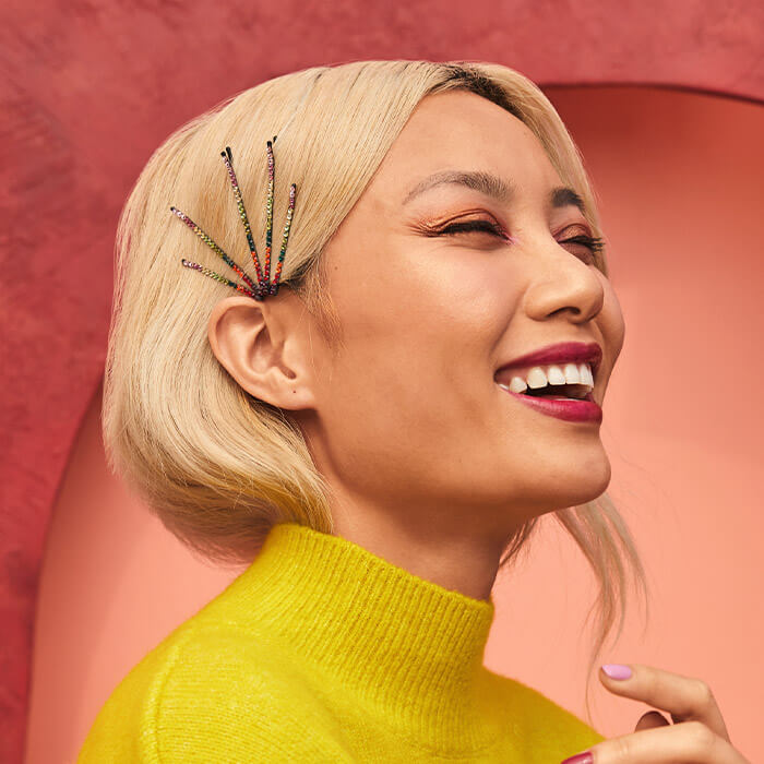 Close-up profile image of a smiling model with blonde hair wearing hair clips embellished with colorful gemstones