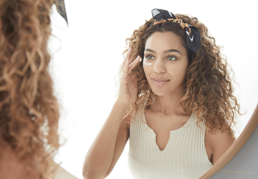 An image of a curly-haired model looking at herself in the mirror while applying cream under her eye