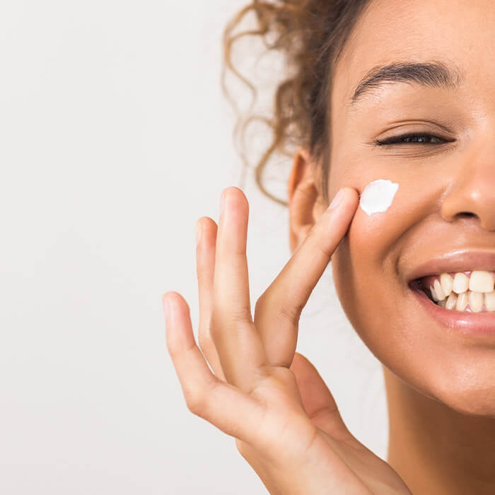 Close-up image of a smiling woman dotting face cream on her cheek