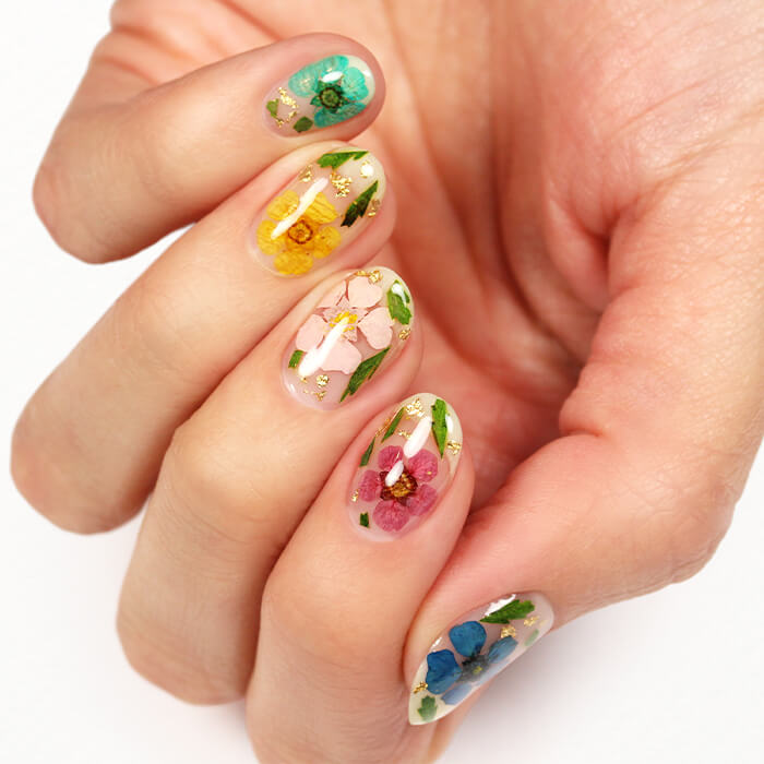 A close-up image of a model's hands with floral nail art
