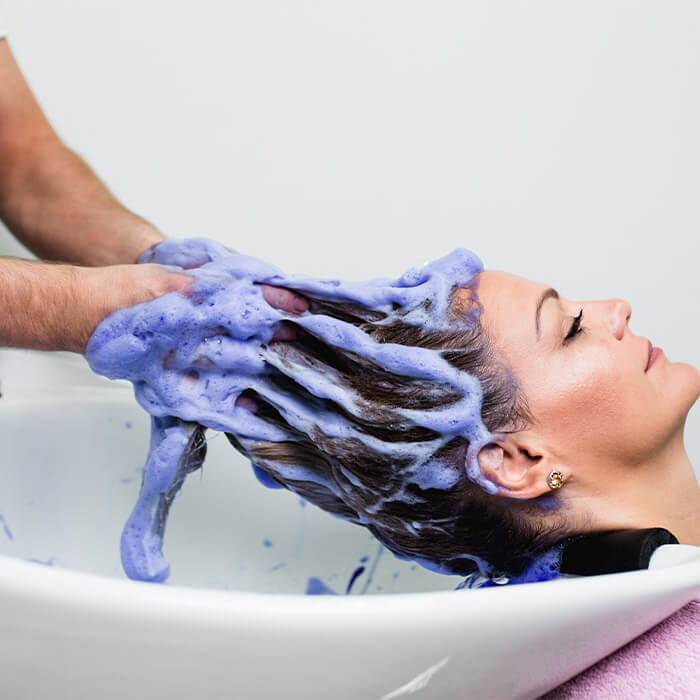 Image of a hairdressing washing woman's hair with purple shampoo in a salon bowl