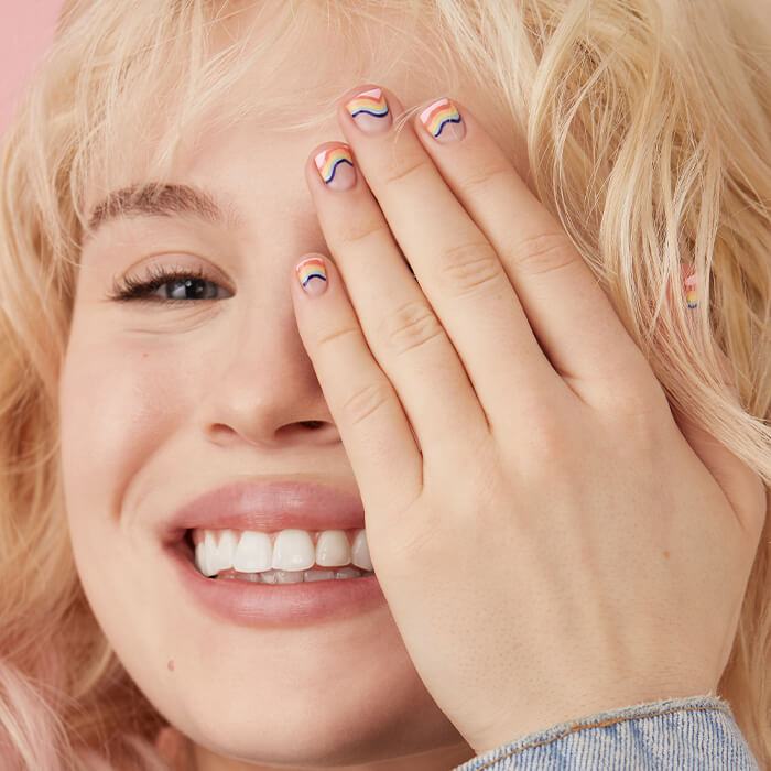 Close-up of a smiling model with colorful nail art covering half of her face with her hand