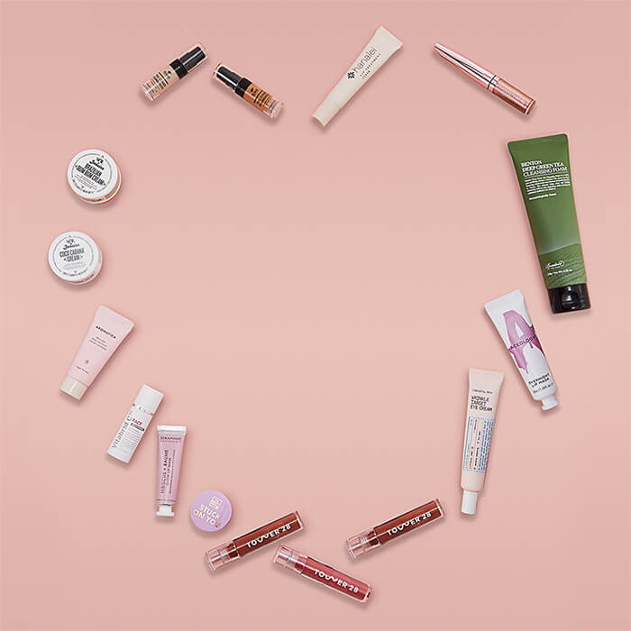 Skincare and makup products arranged in a heart shape on pink background
