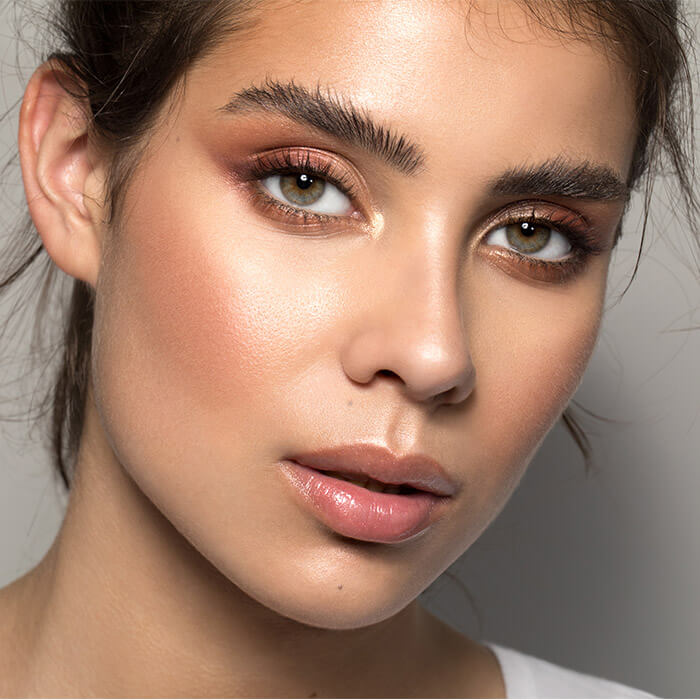 Close-up image of a woman with short hair rocking a copper eyeshadow look and laminated brows
