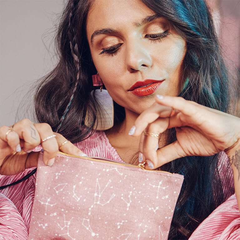 A model opening her pink Glam Bag with a constellations design
