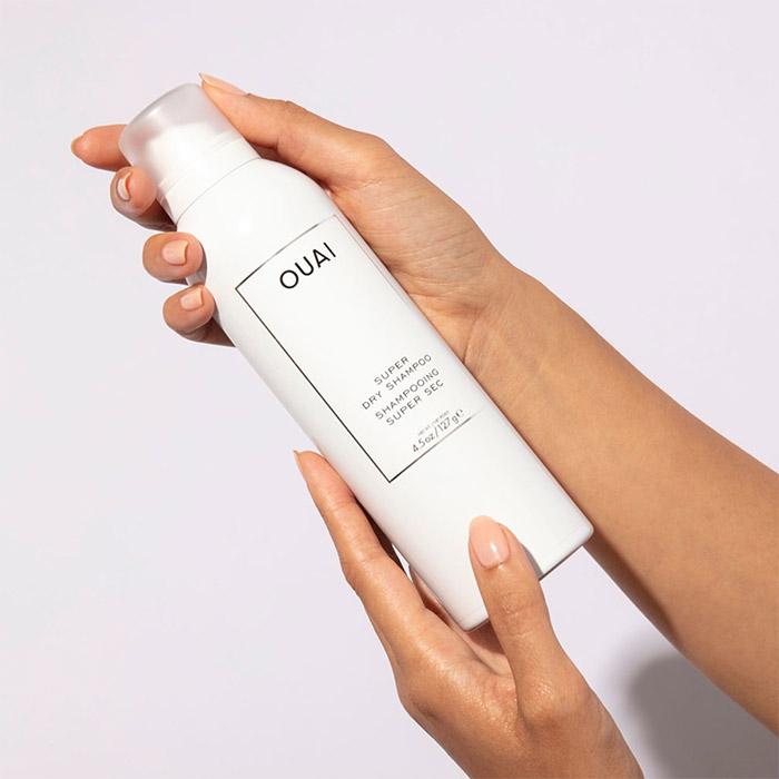 A photo of hands holding an OUAI HAIRCARE Super Dry Shampoo