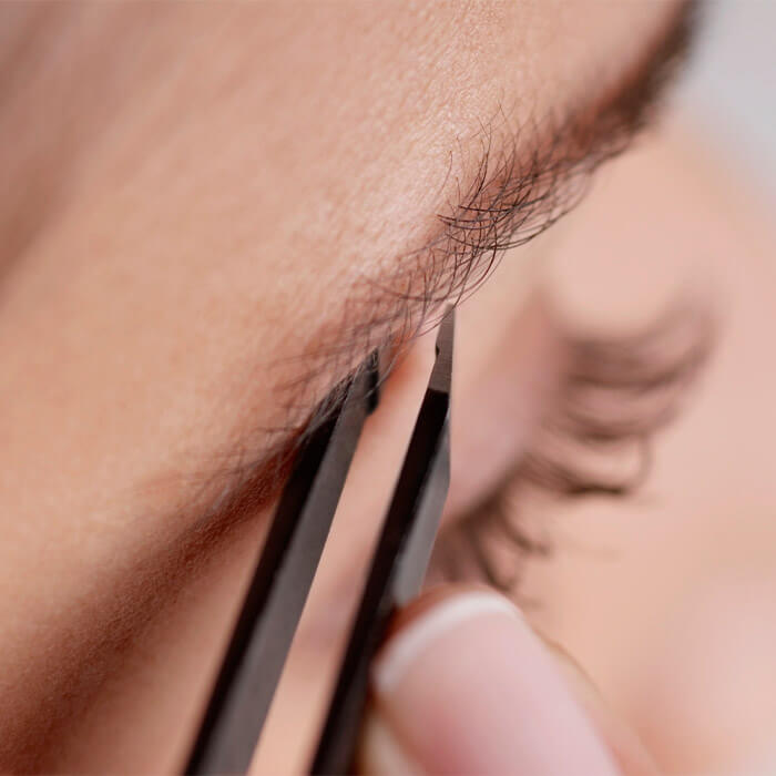 Close-up image of woman tweezing her eyebrows