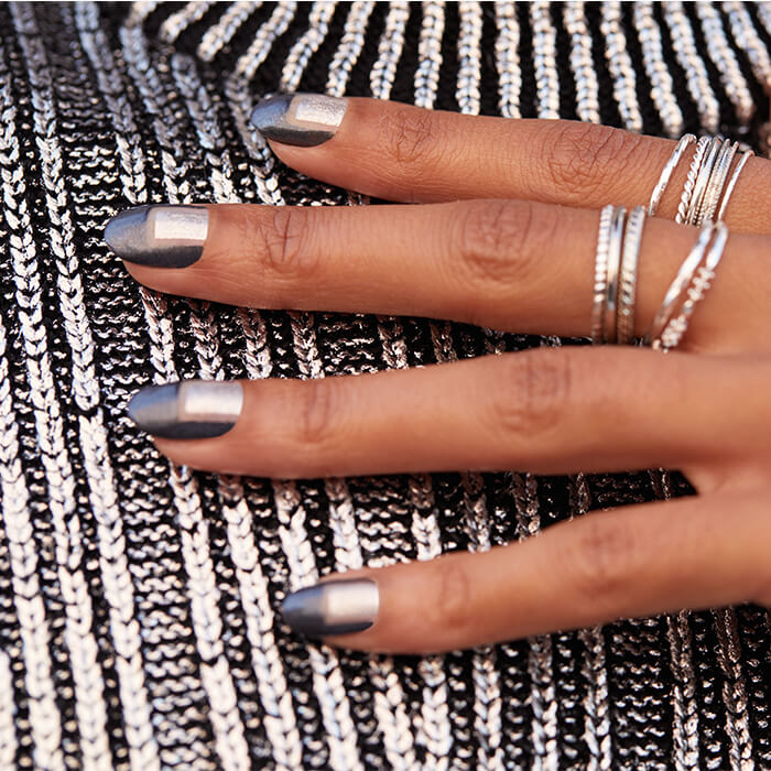 Close-up image of woman's hand with silver rings and metallic negative space nail art mani against sequined black and silver textile