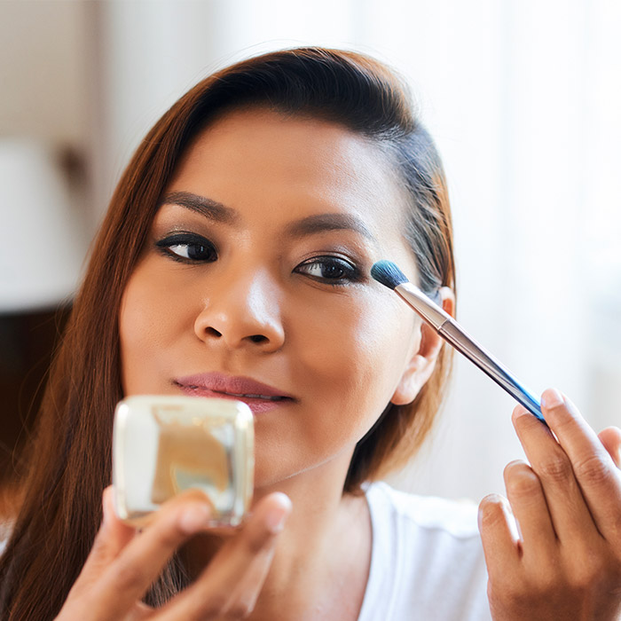 A photo of a woman applying neutral eyeshadow using a makeup brush
