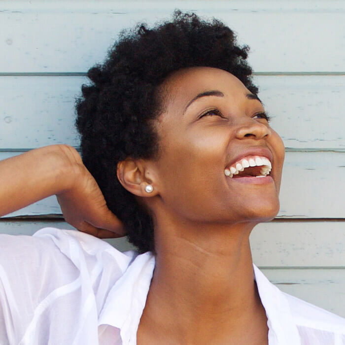 Side profile image of a black woman with short, curly hair in a white top smiling and posing against gray, wooden wall background