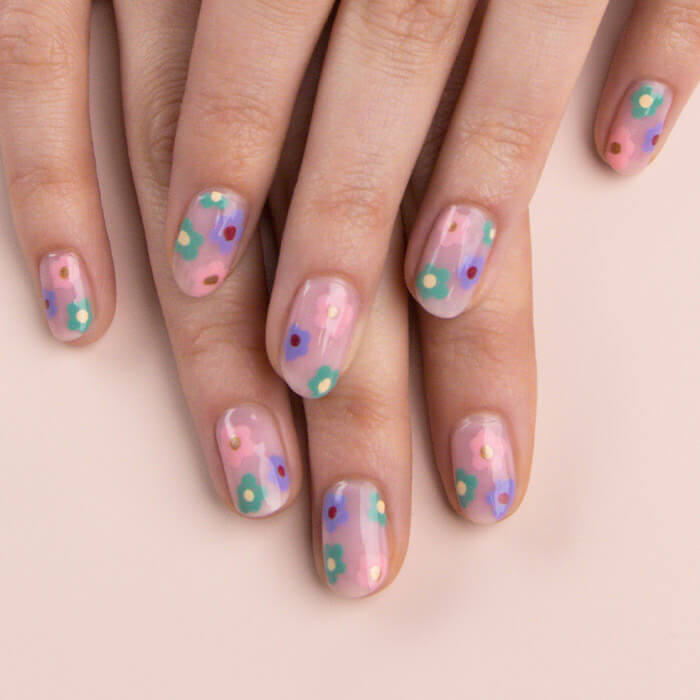 Close-up of model's hands with a purple, pink, and green flower nail art mani on light peach background