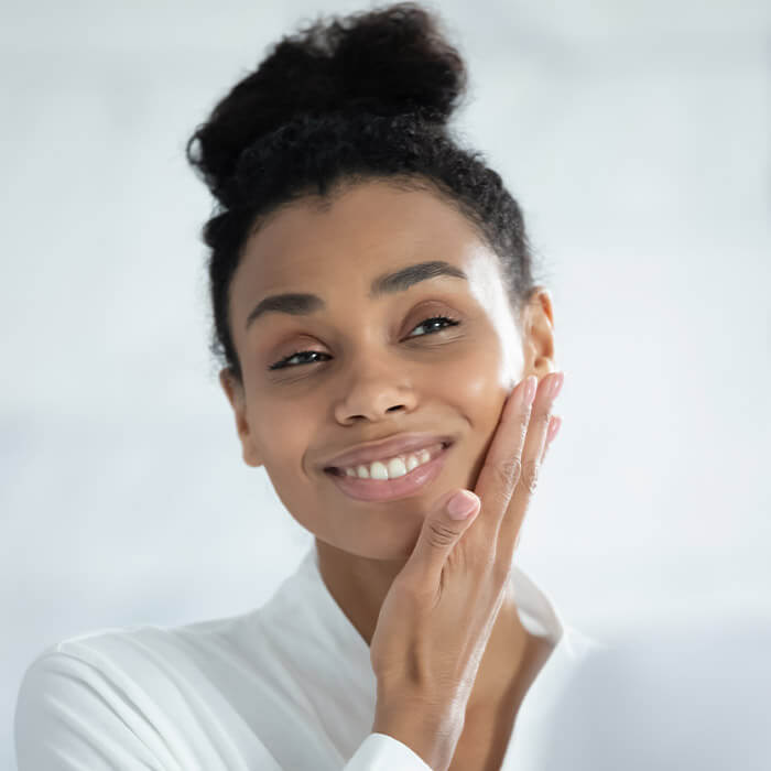 Close-up image of a Black woman touching her smooth face while checking herself in the mirror
