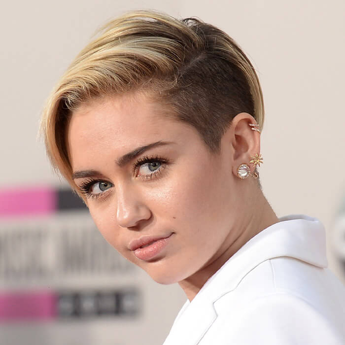 Close-up of Miley Cyrus rocking a long pixie undercut hairstyle and white suit on the red carpet
