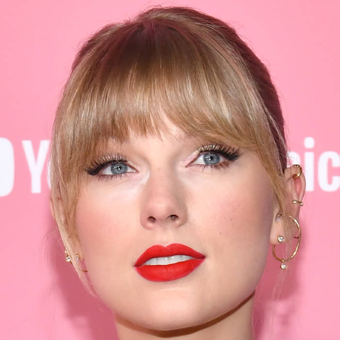 Close-up of Taylor Swift rocking neutral makeup look paired with red lips and sleek hairstyle with bangs