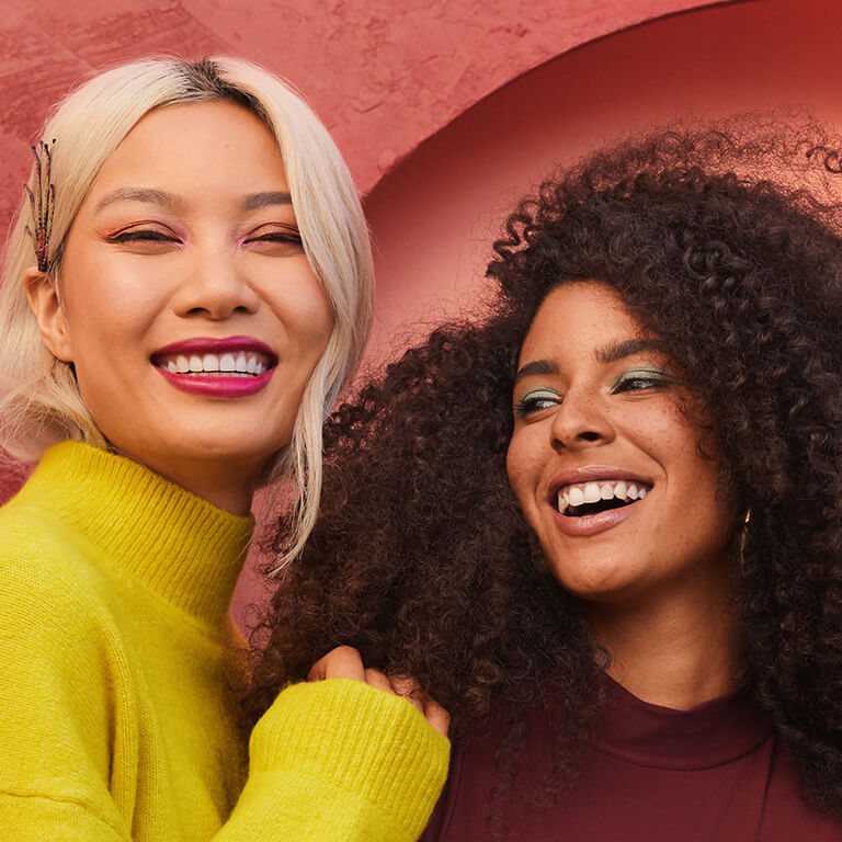 An image of a model with blonde hair and another model with curly hair smiling