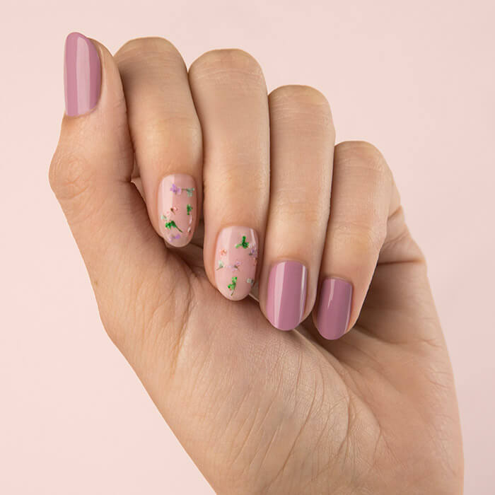Close-up image of a model's clenched hand with pink floral-themed nail art mani on pink background